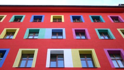 Rotes Haus mit bunten Fensterrahmen